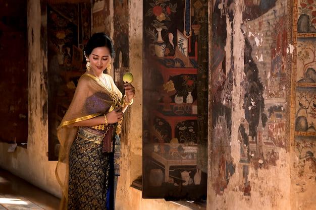 Menina tailandesa das mulheres bonitas que guarda lótus da mão no traje tailandês tradicional com ayutthaya do templo.