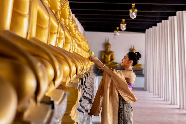 Menina tailandesa das mulheres bonitas que guarda lótus da mão no traje tailandês tradicional.