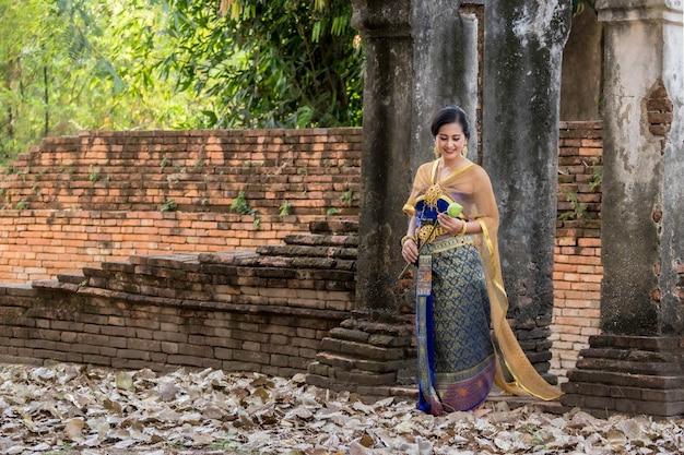 Menina tailandesa de mulheres bonitas segurando lótus de mão em traje tradicional tailandesa com templo ayutthaya
