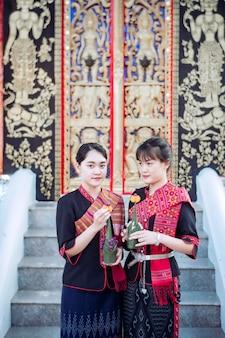 Menina tailandesa na tribo phu thai de pé na área do templo tailandês
