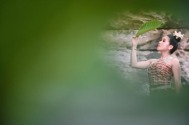 Menina tailandesa no traje tailandês tradicional que olha através do filtro verde da folha das folhas, cultura da identidade de tailândia.