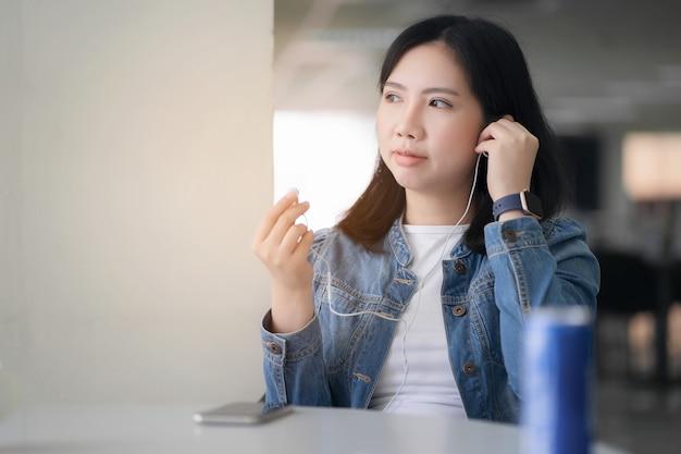 Menina tailandesa relaxa na cafeteria com lata de borrão de cola, ouve música na playlist com fones de ouvido, senta-se contra a grande janela interna, usa jaqueta jeans