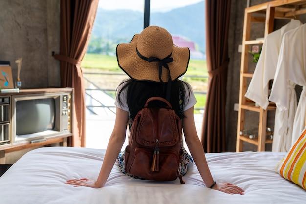 Menina tailandesa relaxar no quarto de cama com fundo do país