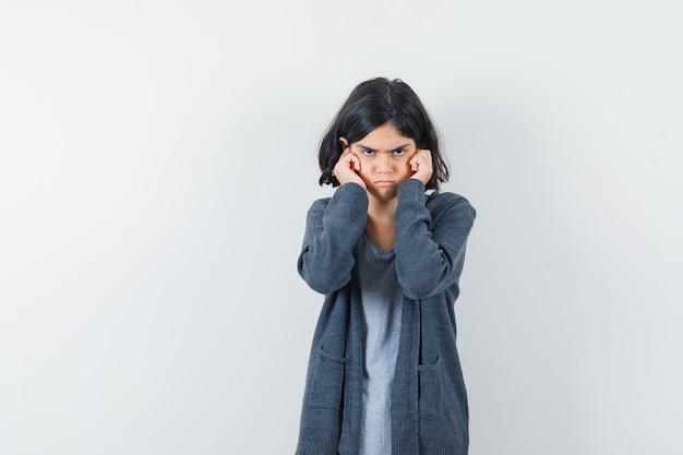 Menina tapando as orelhas com os dedos na camiseta, jaqueta e parecendo teimosa.