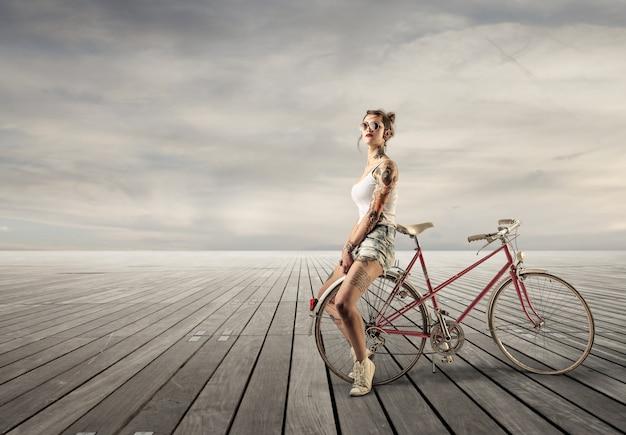 Menina tatuada com uma bicicleta