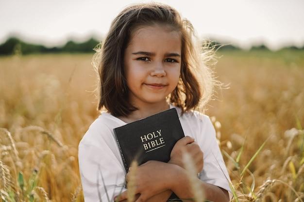 Menina tem a bíblia nas mãos. lendo a bíblia sagrada em um campo. conceito de fé, espiritualidade e religião. paz esperança