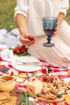Menina tem cerejas maduras suculentas na mão na manta de piquenique quadriculada com comida espalhada nele