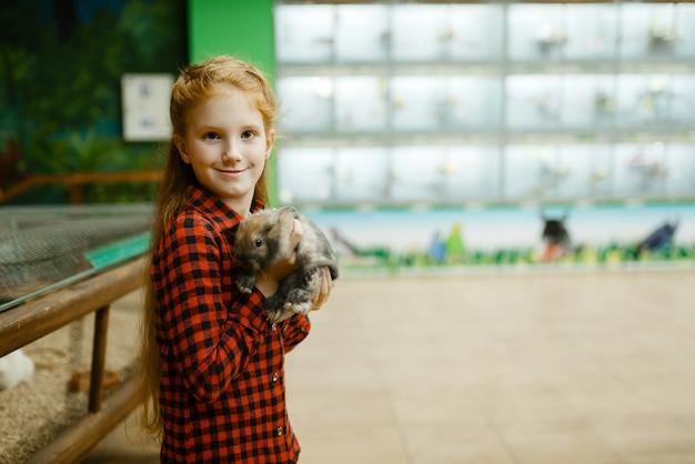 Menina tem coelho nas mãos, loja de animais. criança comprando equipamentos em petshop, acessórios para animais domésticos