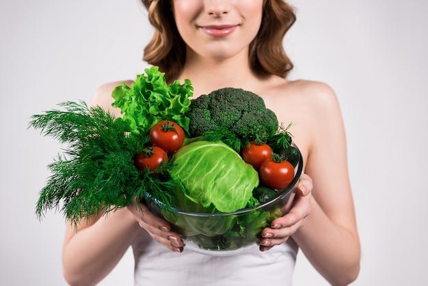 Menina tem legumes frescos nas mãos
