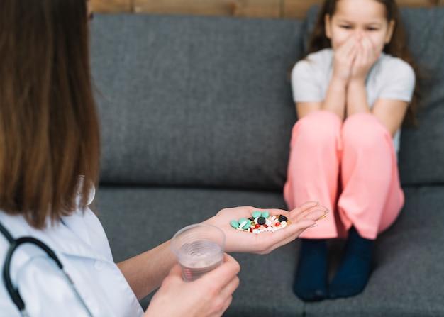Menina tem medo de seu médico feminino dando remédio e copo de água na mão