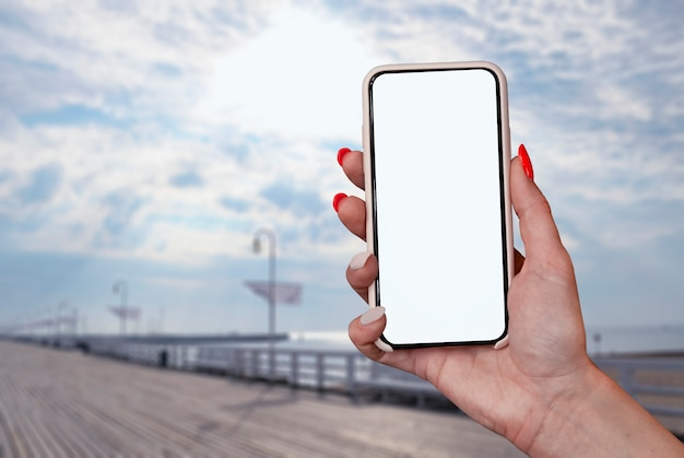 Menina tem na mão um close-up do smartphone, com uma tela branca sobre um fundo de mar. tecnologia mock-up.