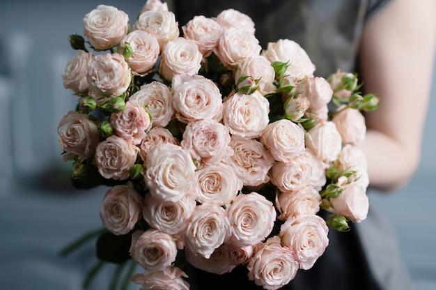 Menina tem nas mãos um lindo buquê de rosas.