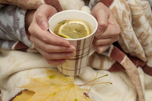 Menina tem nas mãos uma xícara de chá quente com limão.