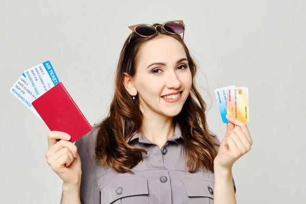 Menina tem passaporte, bilhetes e cartão bancário como um conceito de empréstimo de férias.
