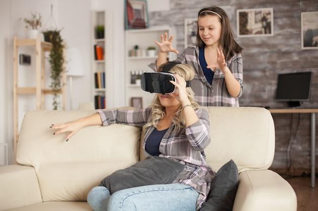 Menina tentando assustar a mãe ao usar fone de ouvido virtual.