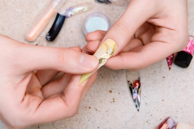 Menina tentando dicas de unhas artificiais com design de unhas de flores