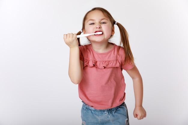 Menina tentando escovar bem os dentes