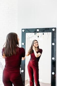 Menina terno vermelho fica espelho frontal, um espelho grande, um reflexo, experimentando um terno, alfaiataria, roupa, indo a uma festa ou a uma festa