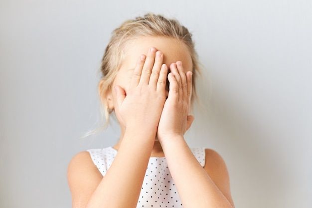 Menina tímida e tímida cobrindo o rosto, sentindo-se assustada. criança do sexo feminino envergonhada posando isolada com as mãos nos olhos, chorando, sentindo vergonha porque a mãe a repreendeu. bebê brincando de esconde-esconde