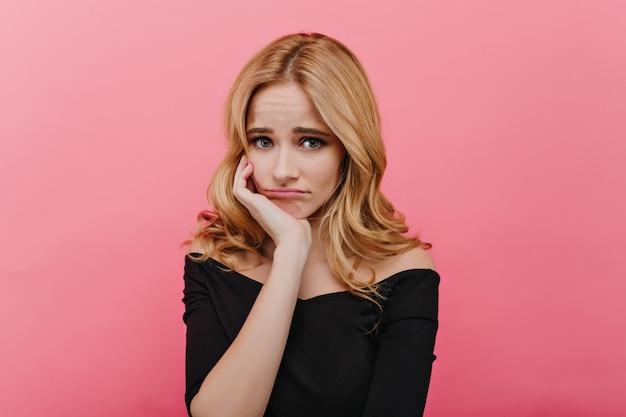 Menina tímida e triste em roupas pretas, sustentando o rosto com a mão. retrato interior de adorável mulher de olhos azuis chateada, posando na parede rosa.