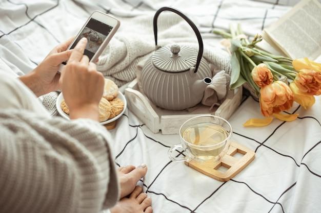 Menina tira fotos ao telefone de uma composição de primavera com chá, biscoitos e tulipas na cama