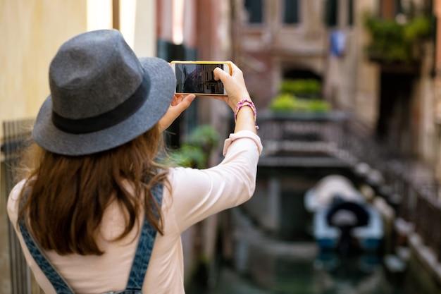 Menina tirando foto de ruas e canais antigos de veneza com smartphone na itália