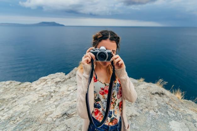 Menina tirando fotos ao ar livre em uma câmera retro nas férias de verão