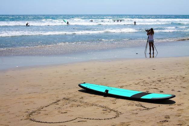 Menina tirando fotos de surfistas iniciantes, prancha de surf na praia e um grande coração desenhado na areia de bali