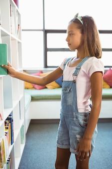 Menina tirando um livro da estante na biblioteca