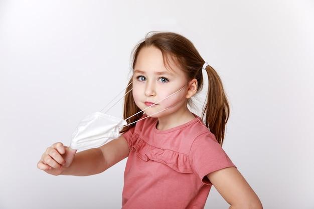 Menina tirando uma máscara médica para respirar melhor
