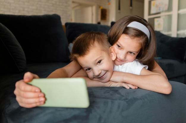 Menina tirando uma selfie em casa com o irmão