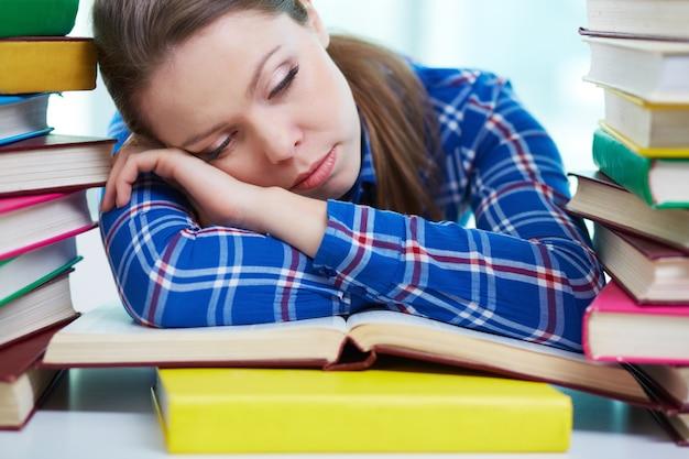 Menina tired que dorme na biblioteca