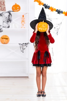 Menina tiro completo, segurando, abóbora halloween
