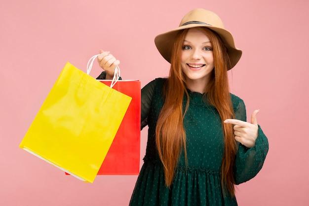 Menina tiro médio, segurando sacolas de compras