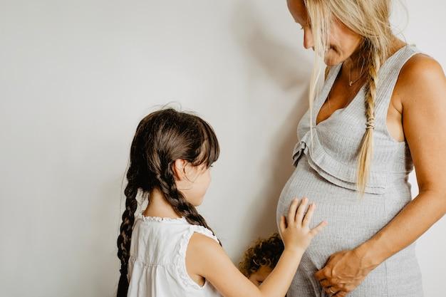 Menina tocando a barriga da mãe grávida
