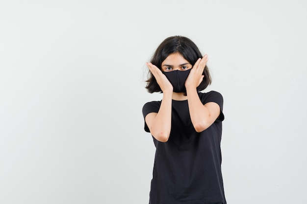 Menina tocando a pele do rosto em camiseta preta, máscara, vista frontal.