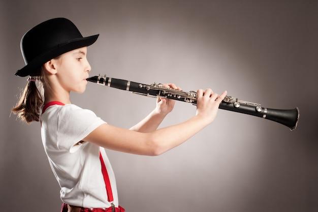 Menina tocando clarinete em cinza