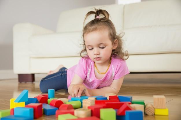 Menina, tocando, com, edifício bloqueia, ligado, chão