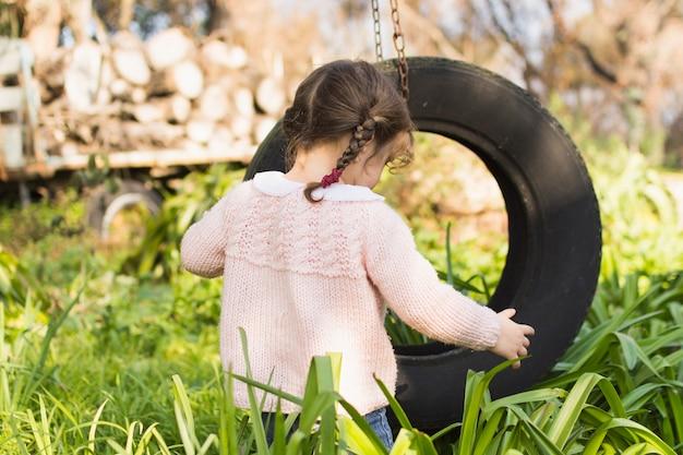 Menina, tocando, com, pneu, em, a, grama verde