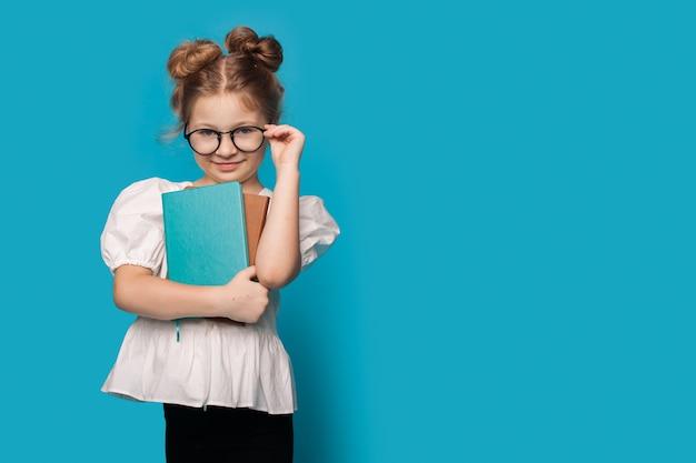 Menina tocando seus óculos e abraçando alguns livros