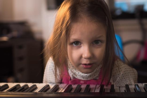 Menina tocando sintetizador de piano em casa, no quarto dela