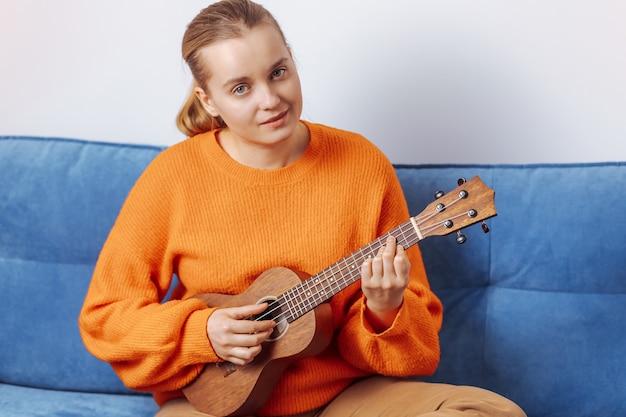 Menina tocando ukulele em casa no sofá