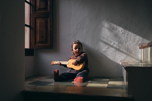 Menina tocando ukulele no chão em casa