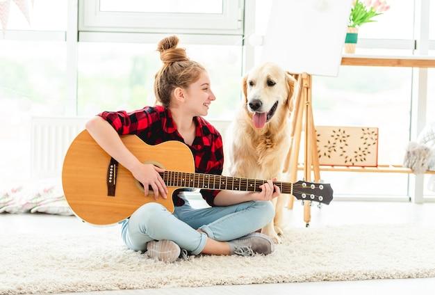 Menina tocando violão com cachorro adorável