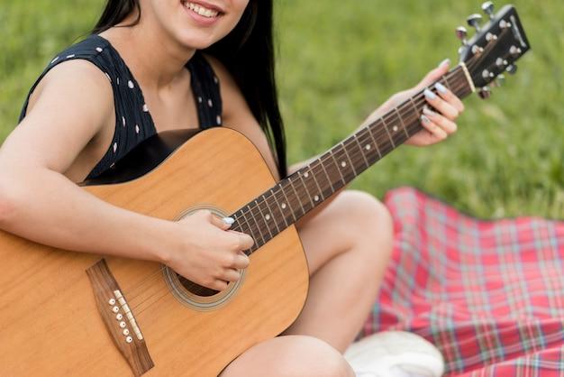 Menina, tocando, violão, ligado, um, piquenique, cobertor