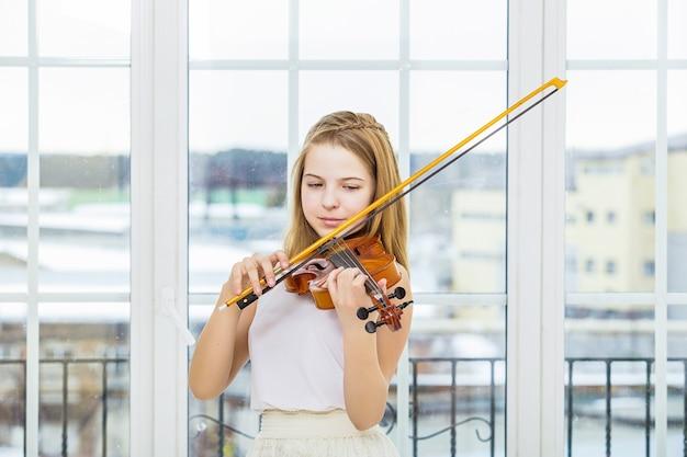 Menina tocando violino para estudar linda e feliz em uma sala branca com uma grande janela