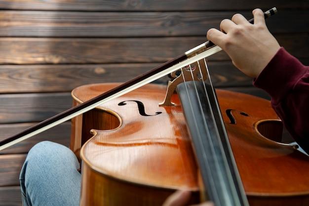 Menina tocando violoncelo no chão de madeira