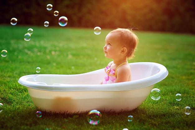 Menina toma banho em uma banheira com bolhas de sabão