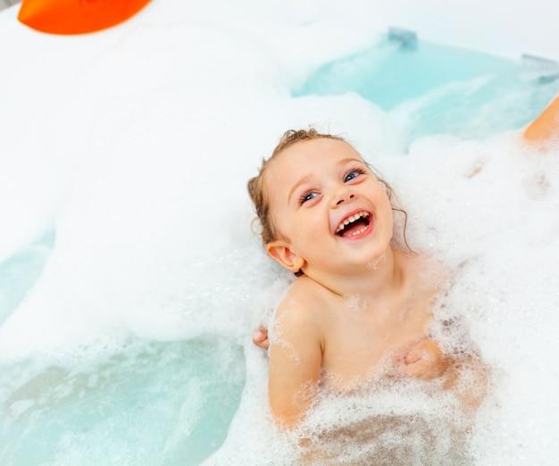 Menina toma banho em uma banheira de hidromassagem.