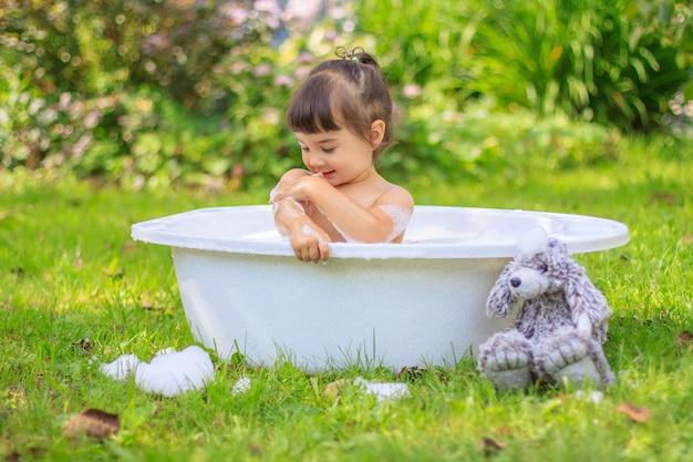 Menina toma banho em uma banheira no jardim de verão